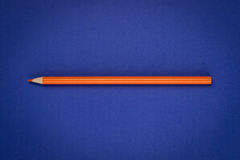 Orange pencil on blue paper. Orange color drawing pencil on blue paper stock photography
