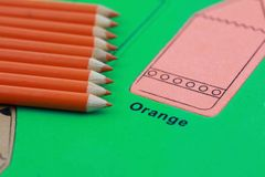 Orange pencil crayon. Many orange pencil crayons On the green color puzzle stock image