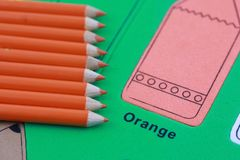 Orange pencil crayon. Many orange pencil crayons On the green color puzzle background royalty free stock images