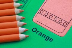 Orange pencil crayon. Many orange pencil crayons On the green color puzzle background stock photo