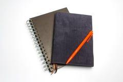 Orange penna på anteckningsboken royaltyfria foton