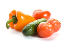 Orange pepper, cucumber and three tomatos Stock Photos