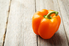 Orange pepper on the grey wooden background Royalty Free Stock Photos
