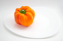 An orange pepper on a white plate. Orange pepper on a white plate  on a white background Royalty Free Stock Images