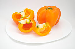 Orange peppers on a white plate. On a white background Royalty Free Stock Image