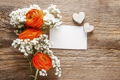Orange persian buttercup flower and baby`s breath on wood Royalty Free Stock Images