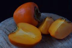 An orange sweet perssimon on a wood. An orange perssimon and three pieces of perssimon on a wood Royalty Free Stock Image