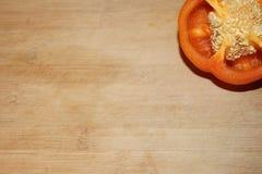 Orange Pfeffer-Schneidebrett-Hintergrund Lizenzfreie Stockbilder