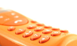 Orange phone detail. An isolated orange phone on a white background and with a shallow depth of field stock photography