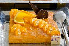 Orange and a piece of orange cake with chocolate topping - finge Stock Photo