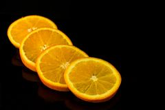 Orange in pieces  on a black background stock photos