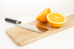 Orange  pieces on a wooden board and knife. Studio shot Stock Images