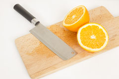 Orange  pieces on a wooden board and knife. Studio shot Royalty Free Stock Image
