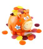 Orange piggy bank with colorful money. On white background Royalty Free Stock Photo