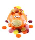 Orange piggy bank with colorful money. On white background Royalty Free Stock Images