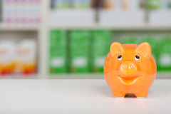 Orange piggy bank on pharmacy counter Stock Photos