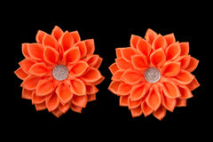 Orange pilbågar av satängbandet Blommor från bandet och bergkristallerna Isolerat på en svart bakgrund Fotografering för Bildbyråer