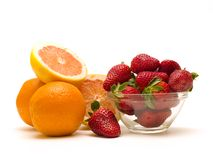 Orange pile. A pile of oranges with strawberries on white background Royalty Free Stock Photo