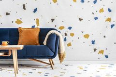 Orange pillow and blanket on navy blue sofa in colorful living room interior with table. Real photo stock photography