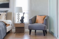 Orange pillow on modern grey chair with bedside table and white. Lamp in bedroom at home Stock Photos