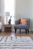 Orange pillow on modern grey chair with bedside table and white Stock Photo