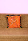 Orange pillow on a sofa isolated against white Royalty Free Stock Image