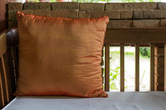 Orange pillow on wooden couch Stock Image