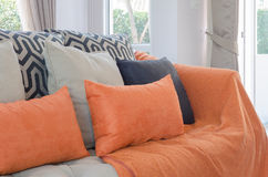 Orange pillows and blanket on modern sofa in living room Stock Photos
