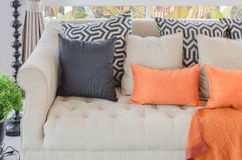 Orange pillows and blanket on modern sofa in living room Royalty Free Stock Photography