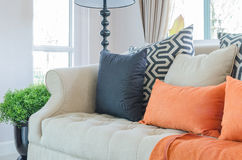Orange pillows and blanket on modern sofa in living room Stock Photography