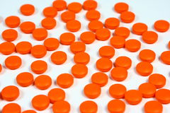 Orange Pills Background. Round orange pills scattered on a white background Royalty Free Stock Photos