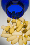 Orange pills in blue bottle vertical. Orange capsules pouring out of a blue bottle on neutral background royalty free stock image