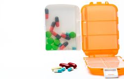 Orange pills box with colorful capsule pills isolated on white background with copy space. Prepare medicine before work or travel abroad concept Stock Images