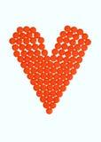Orange pills of love. An arrangement of little orange pills into a heart, on white Royalty Free Stock Photos