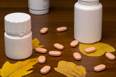 Orange pills and medicine bottle on wooden Stock Images