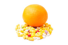 Orange on pills. Perfect orange on bunch of colored pills isolated on white background Royalty Free Stock Photos