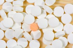 Orange pills are on a pile of white pills Stock Photography