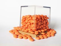 Orange pills in a transparent glass cube. Orange pills pilling in an open transparent glass cube on white background Royalty Free Stock Image