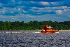 Orange pilot boat in action. Orange pilot boat moving by the river in Europe. Rescue service Royalty Free Stock Photo