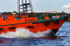 Orange pilot boat in action. Orange pilot boat moving by the river in Europe. Rescue service Royalty Free Stock Photography