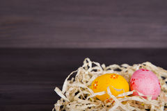 Orange and pink Easter eggs in straw on dark wooden background Stock Photo