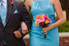 Bridesmaid and groomsman walking down the aisle with colorful bo. An orange, pink, red, yellow bouquet being held by a bridesmaid wearing a blue dress walking royalty free stock photography