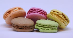 Orange, pink, yellow, brown and green macarons on white. Orange, pink, yellow, brown and green macarons on white Royalty Free Stock Photos