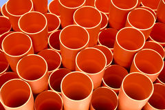 Orange Pipes. Plastic pvc pipes stacked at a construction site Stock Photos