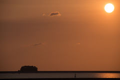 Orange plain sky with quarter sunset one small cloud and black contrast sand bar with strip or water Stock Images