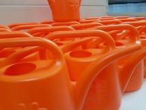 Orange plast- som bevattnar cans för att inge växter Instrument av arbete för jordbruk och kurtis för roomplants royaltyfri foto
