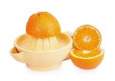 Orange plastic citrus juicer and oranges Stock Photo