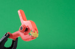 An orange plastic clamps. An orange plastic clamp being supported by a black clamp on a green background. The clamps are employed by hobbyists and professionals royalty free stock photo