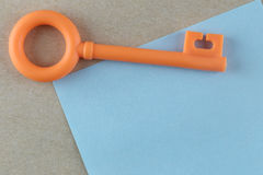 Orange Plastic key is placed on Blue Paper Note. Stock Photography