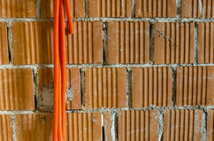 Orange plastic pipes hanging from brick wall Stock Images